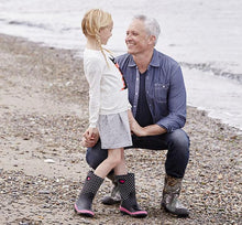 Kid and her dad at the beach smiling at each other while modeling neoprene boots for Western Chief.