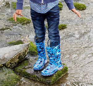 Close up of a model in Western Chief's blue Shark Chase Lighted Rain Boot.