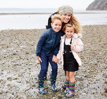 A family poses together at the beach, wearing warm outfits and Western Chief rain boots.
