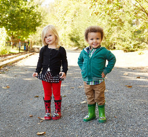 Two kids walking on a gravel road modeling off fun outfits and Western Chief rain boots.