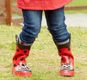 Girl standing in the field with red coat, denim blue jeans, and ladybug rain boots.