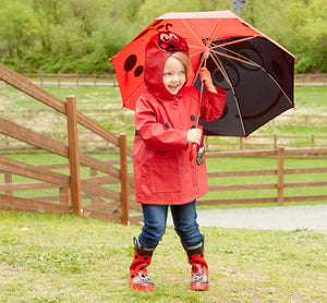 Girl playing outside in the Ladybug Rain Gear Set from Western Chief.