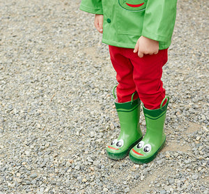 Kid standing on gravel road in red pants, green coat, and green frog rain boots.