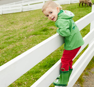 Kid standing on fence wearing Western Chief frog rain coat, red pants, and frog rain boots.