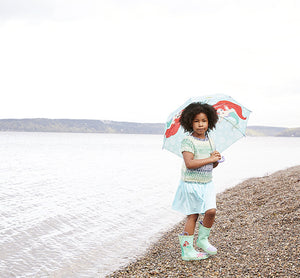 Girl stands by the beach modeling the Western Chief Ariel Rain Boots in aqua and umbrella.