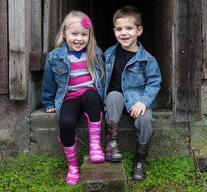Two kids sit outside in t-shirt, jeans, and Western Chief Lighted Rain Boots - Camo print, in pink and green.