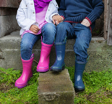 Lifestyle image focusing on pink and navy solid rain boots on two models.