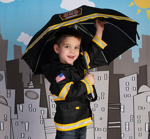 Kid in Western Chief F.D.U.S.A Rain Gear Set standing against city backdrop.