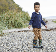 Boy standing at a beach on rocks in warm outfit and dinosaur rain boots.