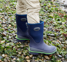 Lifestyle image focusing on the navy neoprene boots a model is wearing.