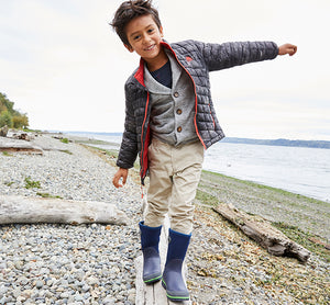 Lifestyle image showing a kid walking on a log in a warm outfit, smiling, modeling off navy neoprene boots.