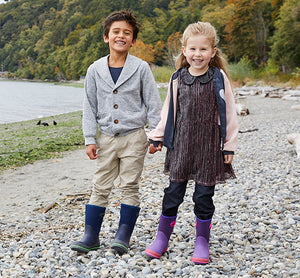Two kids at the beach standing close to a log in warm outfits and Western Chief solid neoprene boots.