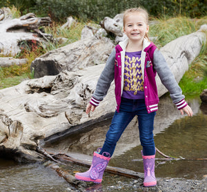 A smiling model smiles at the camera while standing on rocks in water with her butterfly rain boots.