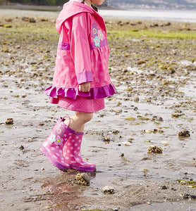 A girl modeling off her Flower Cutie Rain Boots and matching coat from Western Chief.