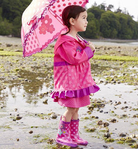A girl at the beach modeling off her pink Western Chief Flower Cutie Rain Gear Set.