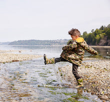 Kid in camo rain gear set jumping around in water.