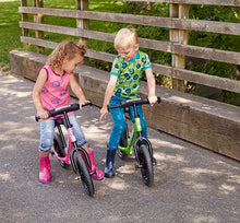 Two kids riding bicycles and wearing solid kids rain boots.