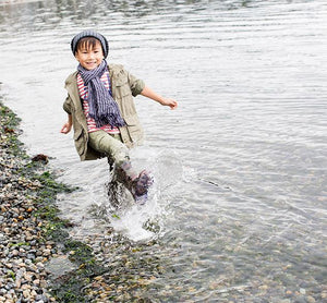 Boy jumps in water with waterproof camo light up rain boots from Western Chief.