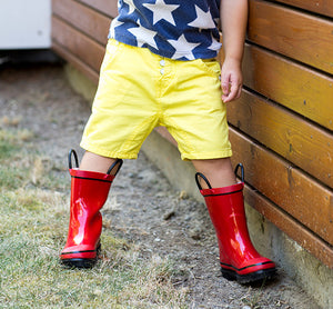 Boy standing modeling the Western Chief Firechief Rain Boots - Red with yellow shorts and blue shirt.