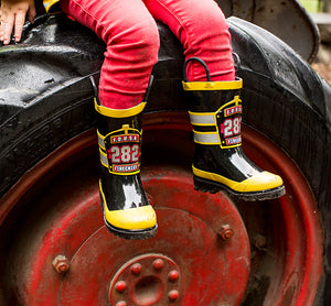 Kid sitting on top of tractor tire in black FDUSA rain boots from Western Chief.