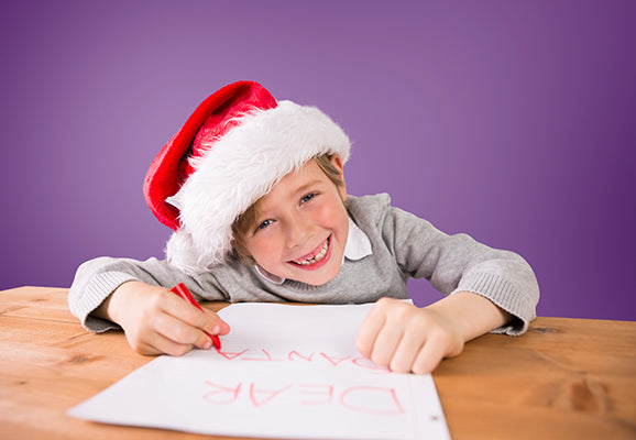 Composite image of festive boy writing letter