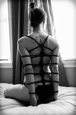 Woman in bondage with hands bound behind her back with beautiful knots.