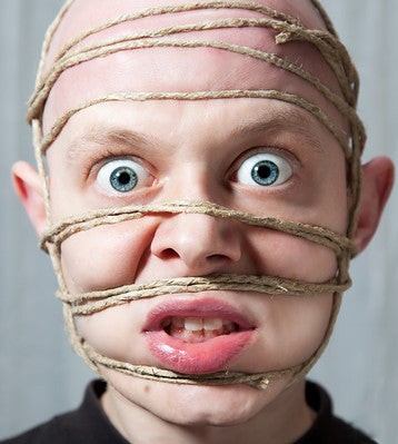 Man looking shocked with his face in bondage ropes.