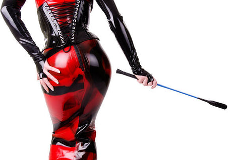A dominatrix with her hand on her behind carrying her BDSM tool of choice.