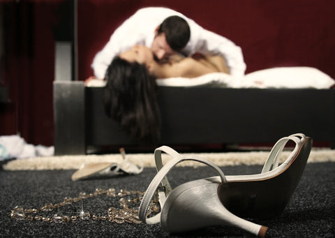 Couple in bed intimately with a shoe on the floor.