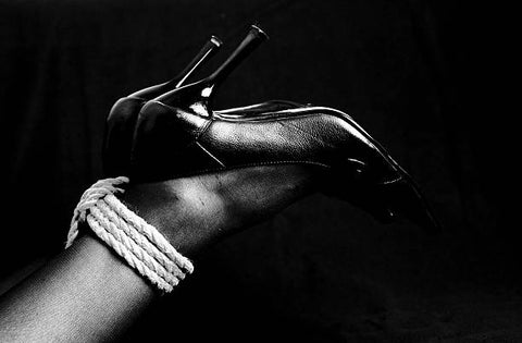 Woman's ankles tied up with a natural fiber rope.