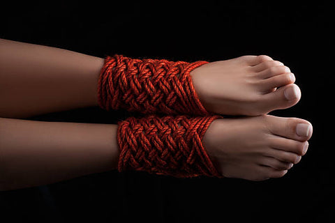 Ankles beautifully bound in red ropes.