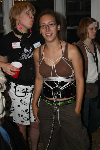 A lady with a bondage harness with a group of people from the bondage community.