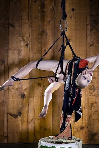 A woman suspended in the art of Shibari.