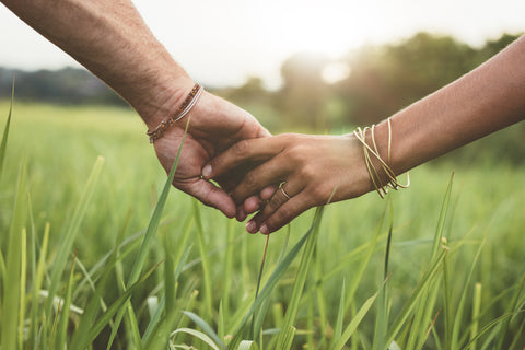 Knotty Desires couple holding hands in a field.