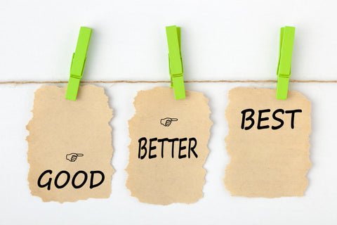 Signs hanging from clothes pins that say good, better, best.