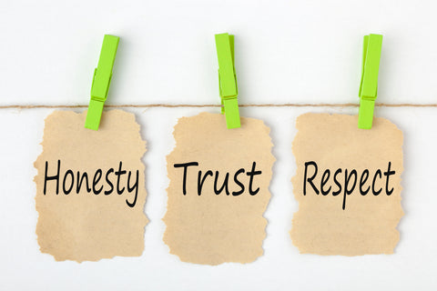 Signs hanging from clothes pins with the words honesty, trust, respect.
