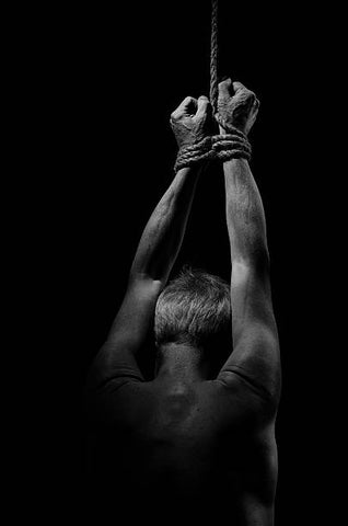 A man with his hands tied down to a hard point.