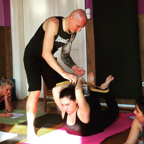 Woman practicing yoga with an instructor with a strap to increase flexibility.