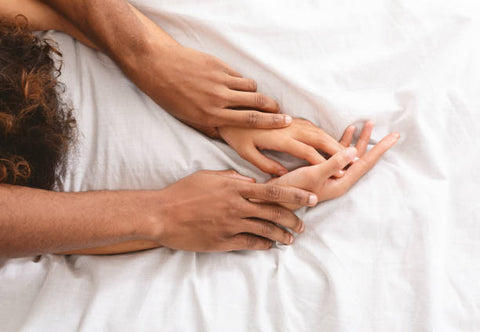 A couples hands on a bed.