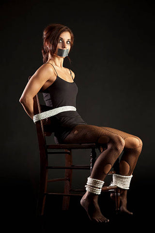 A woman tied down to a chair.