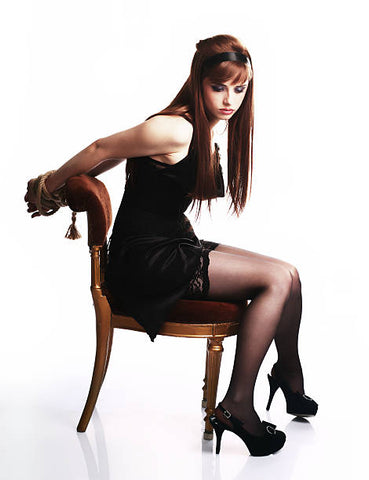 Woman sitting on a chair with her wrists bound behind her.