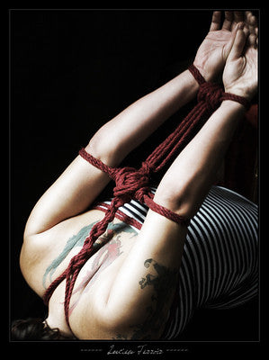 Woman on the floor with her arms bound in Twisted Cotton Bondage Rope.