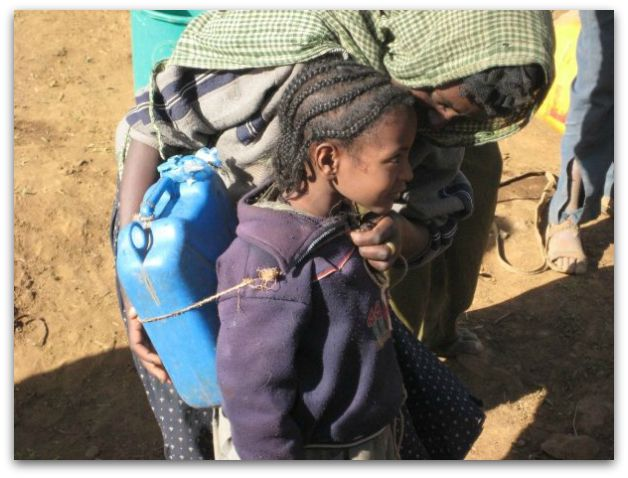Small Ethiopian girl carrying water with a jerry can