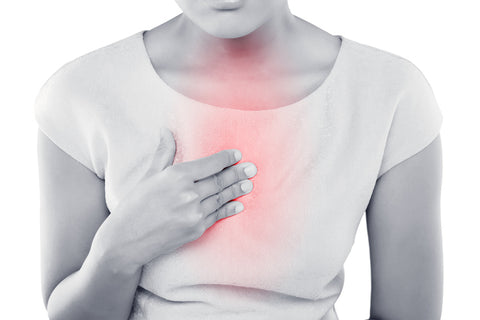 Women rubbing chest from heartburn