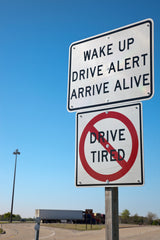 Street signs warning not to drive tired.