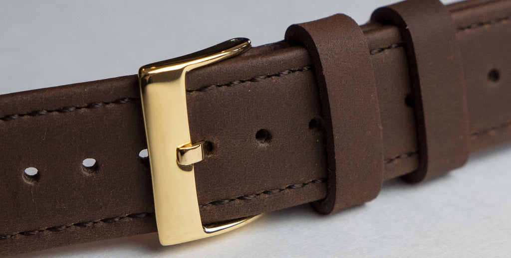 gold buckle on saddle leather