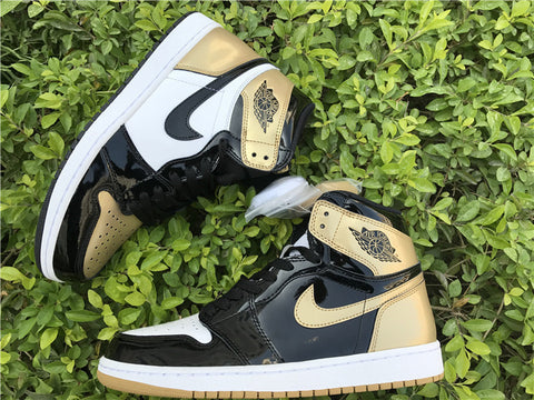 19fc99eaa76b77 The shoe features a mix of black and gold patent leather