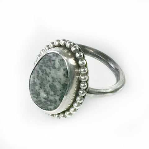 BLACK AND GREY SPECKLED BEACHSTONE RING WITH BEADED SURROUND
