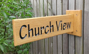 Solid oak wooden sign extruding from a solid oak backplate which is attached to the surface with four simple screw fixings, providing a 180 view, with engraved lettering painted with black paint finished with 3 coats of osmo oil.