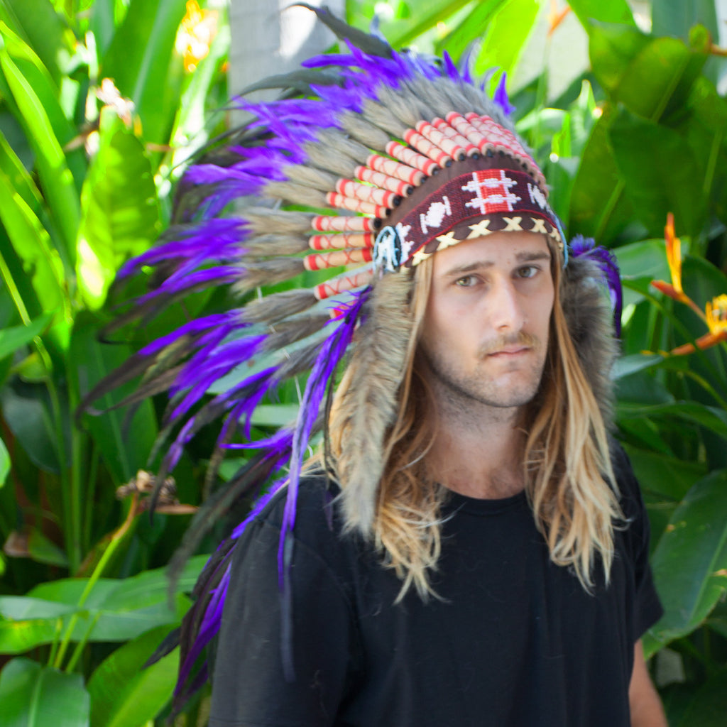 photo of a man wearing long purple indian headdress with beads, leather, and purple rooster feathers with green iridescent tinge, for men, for women, or for children, available for purchase from the sounding iron with shipping from the united states
